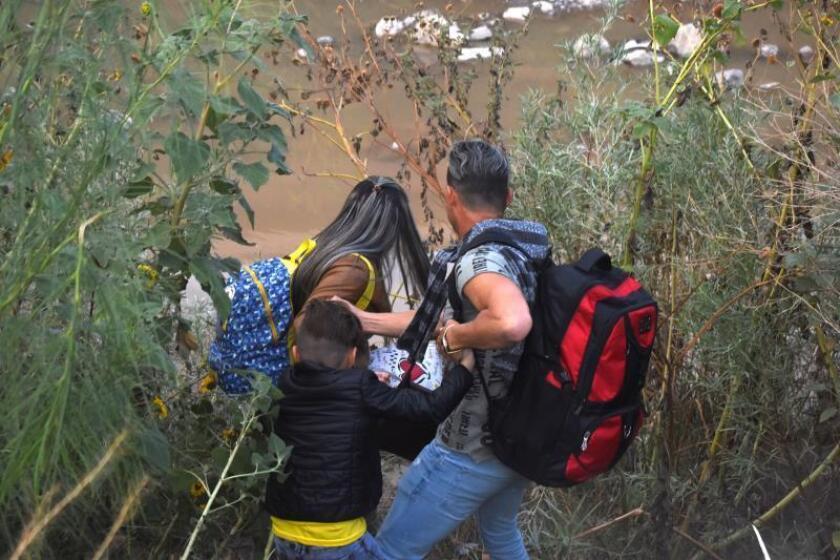 Una familia de migrantes centroamericanos cruzan el Río Bravo, en Ciudad Juárez, Chihuahua (México). En una de las zonas más pobres, donde se encuentran las compuertas del Río Bravo o río Grande, frontera natural entre México y Estados Unidos, la Patrulla Fronteriza estadounidense disparó gas pimienta a algunas personas que se bañaban en el afluente.