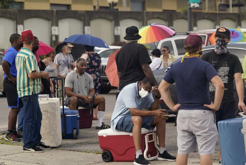 Un grupo de personas hace fila para recibir alimentos y hielo en un centro de distribución