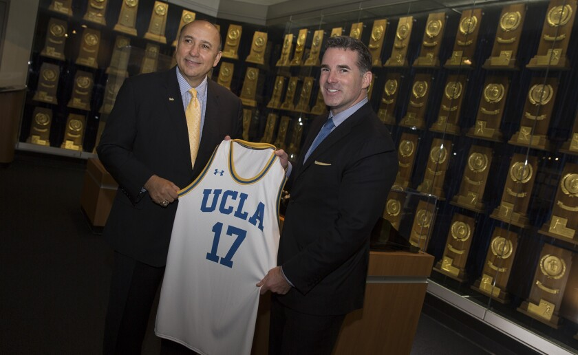 UCLA athletic director Dan Guerrero, left, and Under Armour's Kevin Plank with a UCLA jersey following a meeting and prior to a press conference at the Morgan Center where they officially announced UCLA and Under Armour agreement