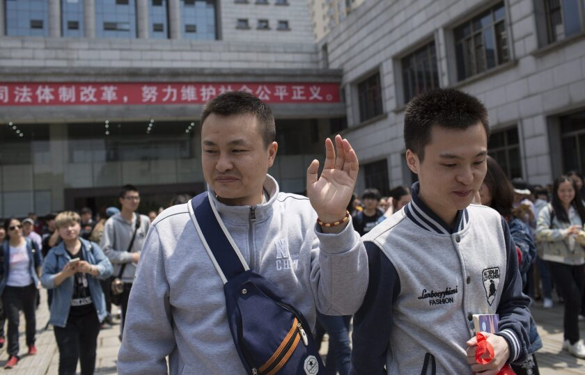 Sun Wenlin, right, and Hu Mingliang leave a courthouse in Changsha, China, after a ruling forbidding the couple to marry.
