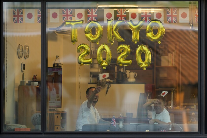 FILE - In this July 23, 2021, file photo, people look out their apartment window from a nearby building before the opening ceremony in the Olympic Stadium at the 2020 Summer Olympics in Tokyo, Japan. (AP Photo/Lee Jin-man, File)