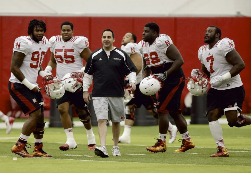 Nebraska defensive coordinator John Papuchis is surrounded by players during practice in Lincoln, Neb., Wednesday, Dec. 10, 2014. Nebraska begins practicing for the Holiday Bowl against USC with interim coach Barney Cotton in charge. Bo Pelini was fired 10 days ago, and new coach Mike Riley is busy