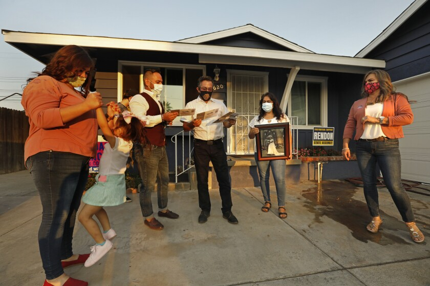 A family, all wearing face masks, stand in front of their house