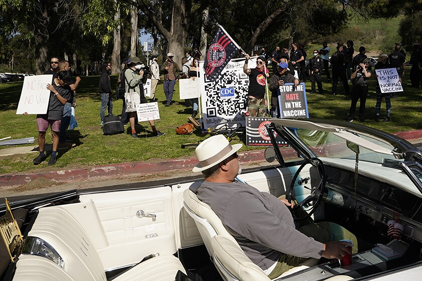"""A car passes a group holding flags and signs that read """"Stop the Hate in the Vaccine"""" and """"This is Not a Normal Vaccine"""""""