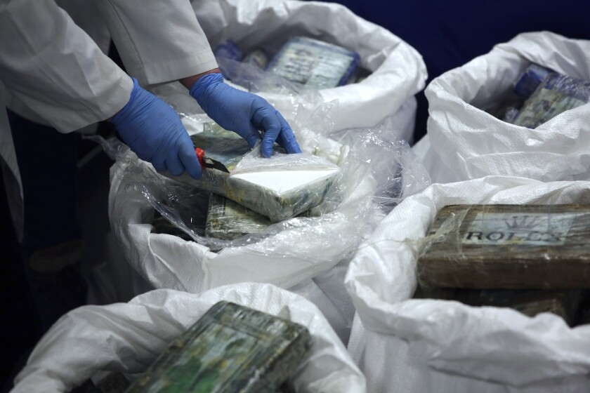 A member of the police opens a packet with cocaine, as a large supply recently seized was displayed to the press at the Portuguese police headquarters in Lisbon, Wednesday, Jan. 8, 2020. For the second time in twelve months, Portuguese police have discovered a large stash of cocaine concealed in a shipment of bananas from Latin America. (AP Photo/Armando Franca)