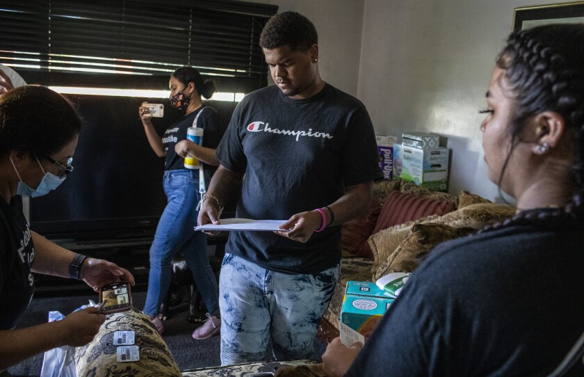 Tomajae Tolliver, center, looks over paperwork with his girlfriend, Katherine Cordova.