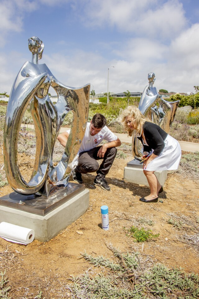 """Artist Lake Daffner speaks with Arlene Greer, chair of the Newport Beach Arts Commission, next to his sculpture """"Wind Swept."""""""
