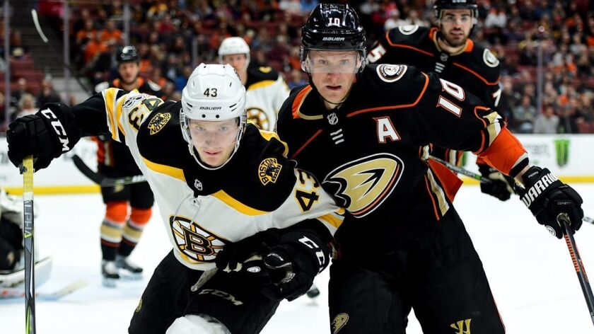 Boston Bruins' Danton Heinen (43) and Ducks' Corey Perry (10) skate after the puck during the second period at Honda Center on Wednesday.