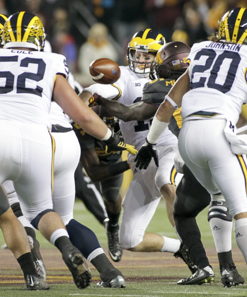 Michigan quarterback Jake Rudock (15) fumbles the ball during the first half of an NCAA college football game Saturday against Minnesota, Oct. 31, 2015, in Minneapolis.(Minnesota recovered the ball.AP Photo/Paul Battaglia)