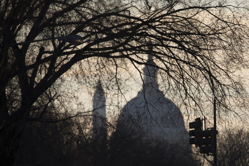 The Capitol building and Washington Monument are seen through trees as the sun sets in Washington.