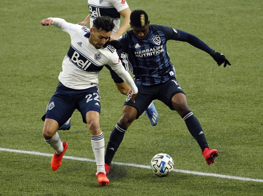 Vancouver Whitecaps defender Erik Godoy, left, and Los Angeles Galaxy midfielder Yony Gonzalez battle for possession during the first half of an MLS soccer match in Portland, Ore., Sunday, Nov. 8, 2020. (AP Photo/Steve Dipaola)