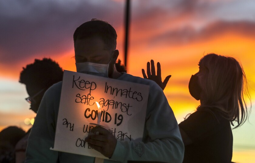 Family members of prison inmates in Utah hold candles following a rally in Draper.