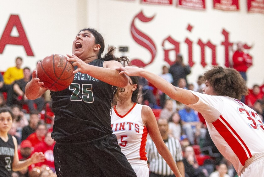 Costa Mesa's Katie Belmontes is fouled by Sanat Ana's Halle Broadnax during an Orange Coast League o