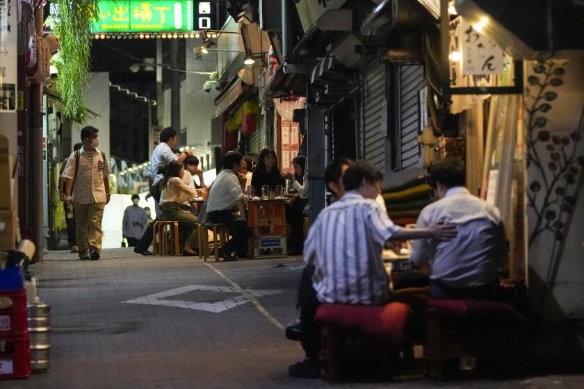 Gente reunida en bares abiertos y que sirven alcohol, en un callejón lleno de bares y restaurantes