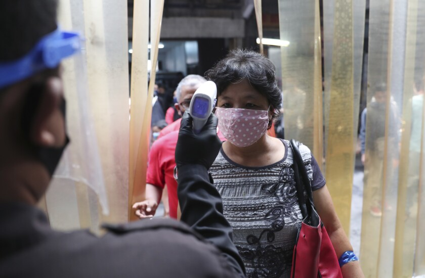 A security guard checks the body temperature of a woman before entering a clothing market to help curb the spread of the coronavirus in Jakarta, Indonesia, Monday, June 15, 2020.(AP Photo/Achmad Ibrahim)