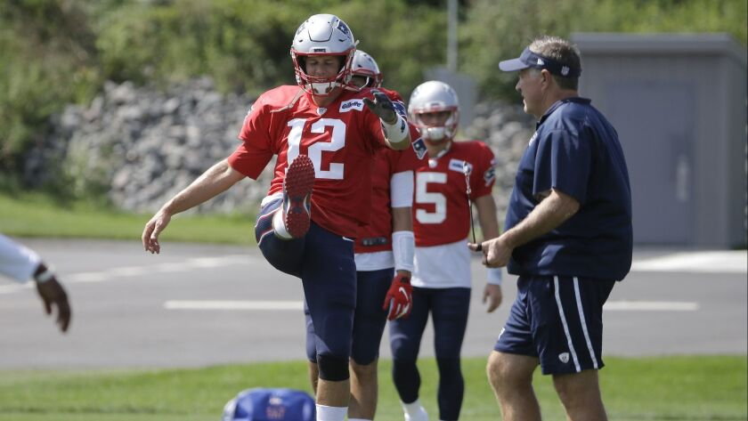 Patriots quarterback Tom Brady (12) warms up as head coach Bill Belichick, right, walks on the field during practice this week.