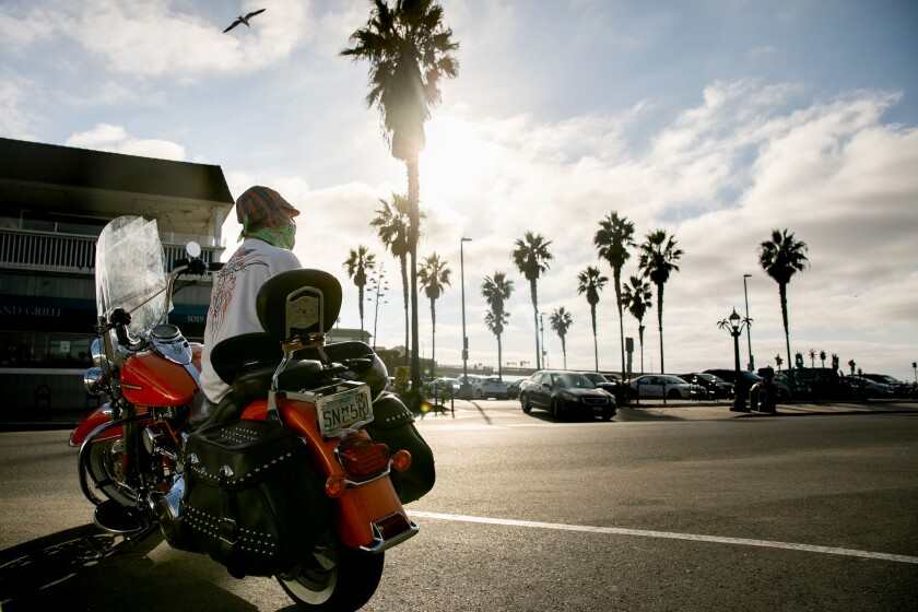 Greg Deyesso dons a face mask and a bandana while sitting on his Harley Davidson motorcycle in Ocean Beach in October 2020.