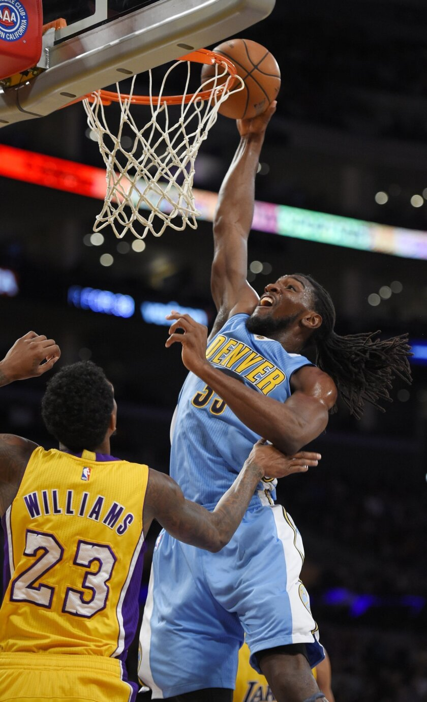 Denver Nuggets forward Kenneth Faried dunks as Los Angeles Lakers guard Lou Williams defends during the first half of an NBA basketball game, Tuesday, Nov. 3, 2015, in Los Angeles. (AP Photo/Mark J. Terrill)