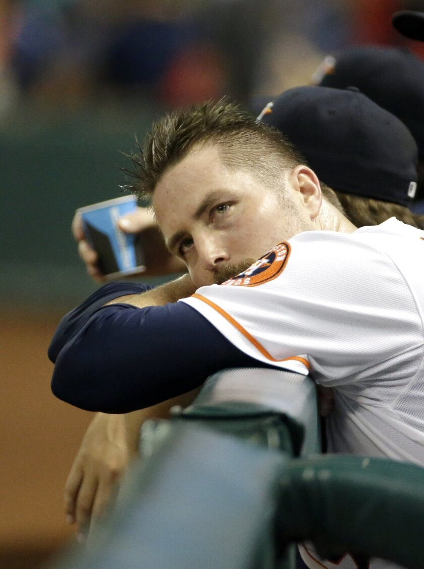 Houston Astros relief pitcher Chad Qualls rests his head on the dugout rail after giving up a home run to Toronto Blue Jays' Nolan Reimold during the ninth inning of a baseball game Thursday, July 31, 2014, in Houston. The Blue Jays won 6-5. (AP Photo/David J. Phillip)