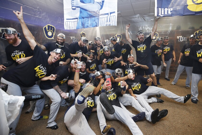 Milwaukee Brewers players celebrate in the clubhouse after clinching a playoff berth following a 9-2 win over the Cincinnati Reds on Wednesday.