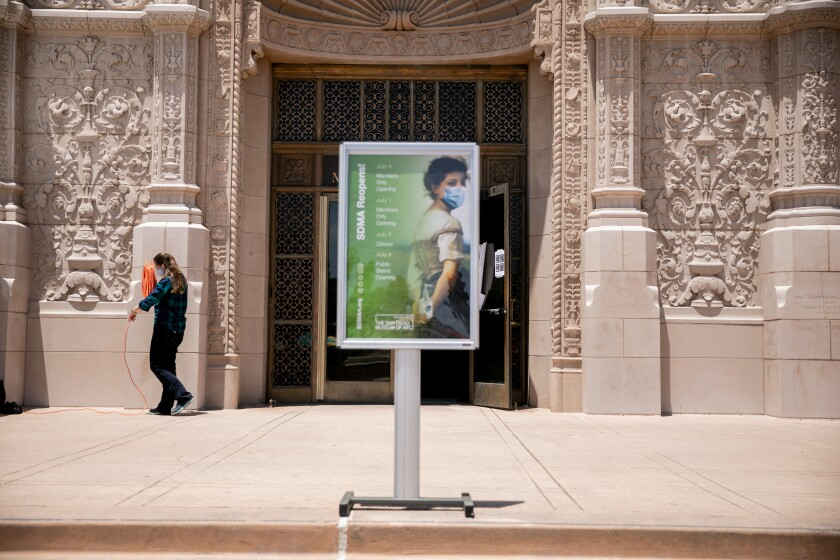 Elyse Adams, lead museum attendant at the San Diego Museum of Art, cleans up in front of the museum.