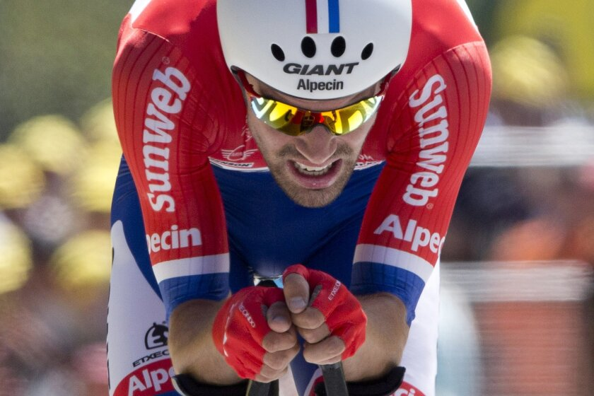 Netherlands' Tom Dumoulin crosses the finish line during the thirteenth stage of the Tour de France cycling race, an individual time trial over 37.5 kilometers (23 miles) with start in Bourg-Saint-Andeol and finish in La Caverne du Pont-d'Arc, France, Friday, July 15, 2016. (AP Photo/Peter Dejong)