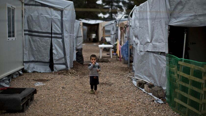 A Syrian child walks between shelters at a refugee camp located north of Athens, Greece, on Dec. 28.