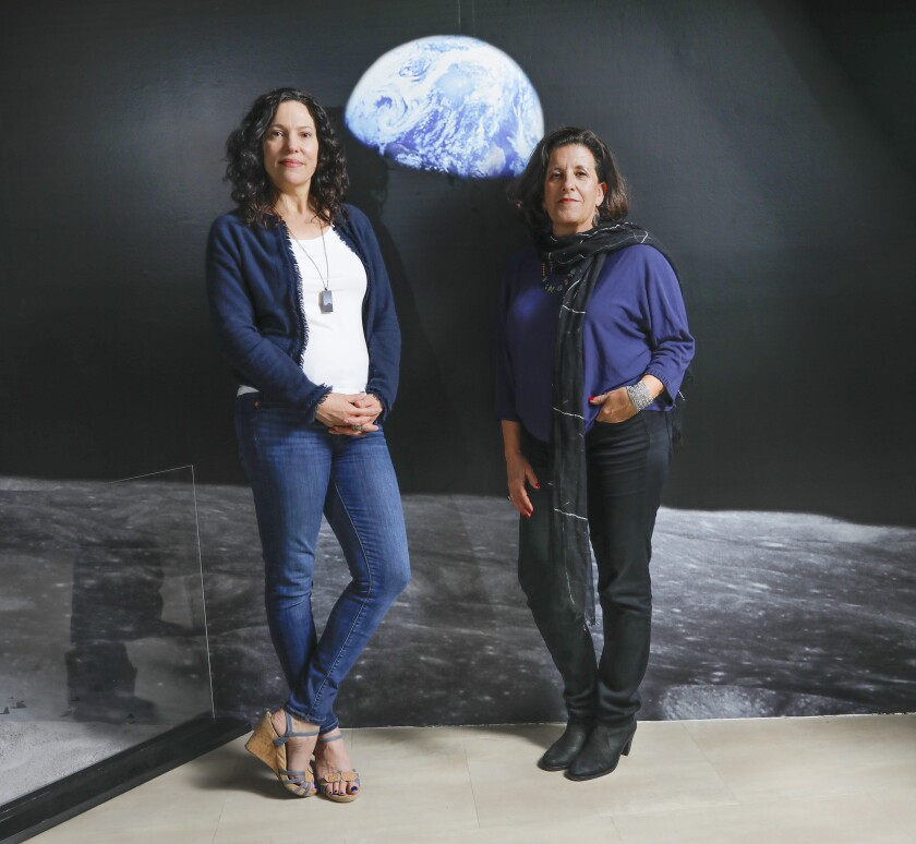 """""""They Promised Her the Moon"""" director Giovanna Sardelli (left) and playwright Laurel Ollstein, in front of the famous """"Earthrise"""" photograph on display at the San Diego Air & Space Museum."""