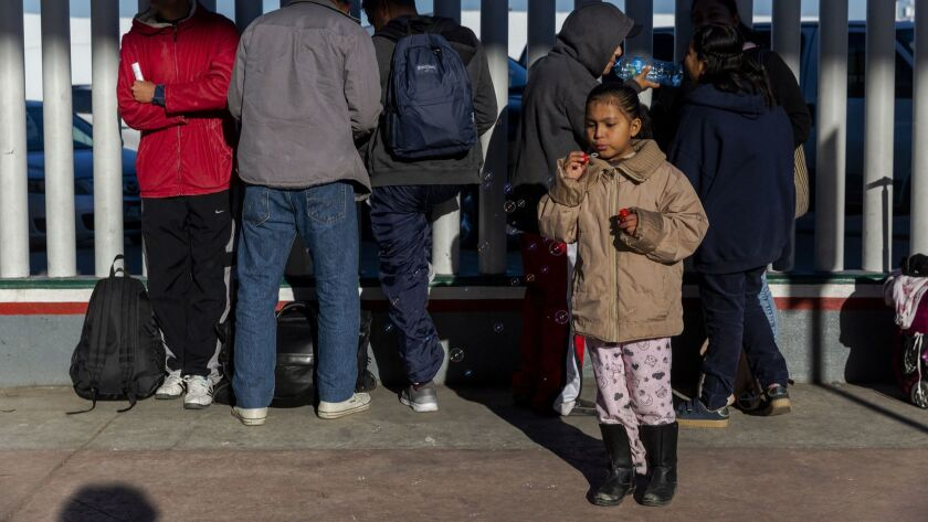 Asylum seekers line up outside the El Chaparral border crossing, as they wait for their numbers to be called so they can be processed, in Tijuana, Baja California State, Mexico.