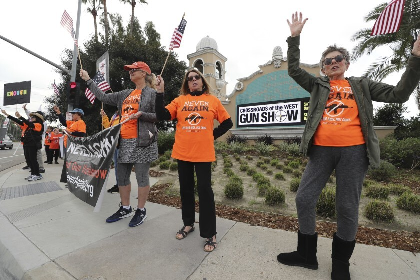 Alice McNally, right, Jane Stro, second from right, and Jill Cooper wave as motorists pass by outside the Crossroads of the West Gun Show at the Del Mar Fairgrounds in December.