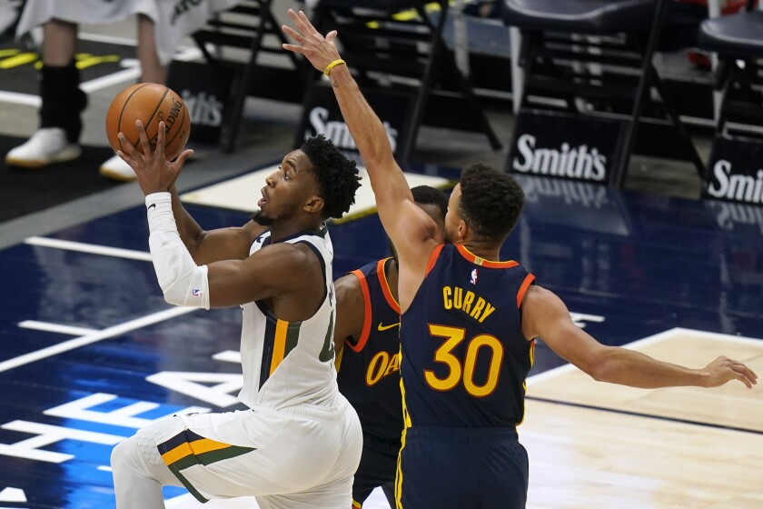 Utah Jazz guard Donovan Mitchell (45) goes to the basket as Golden State Warriors guard Stephen Curry (30) defends during the first half of an NBA basketball game Saturday, Jan. 23, 2021, in Salt Lake City. (AP Photo/Rick Bowmer)