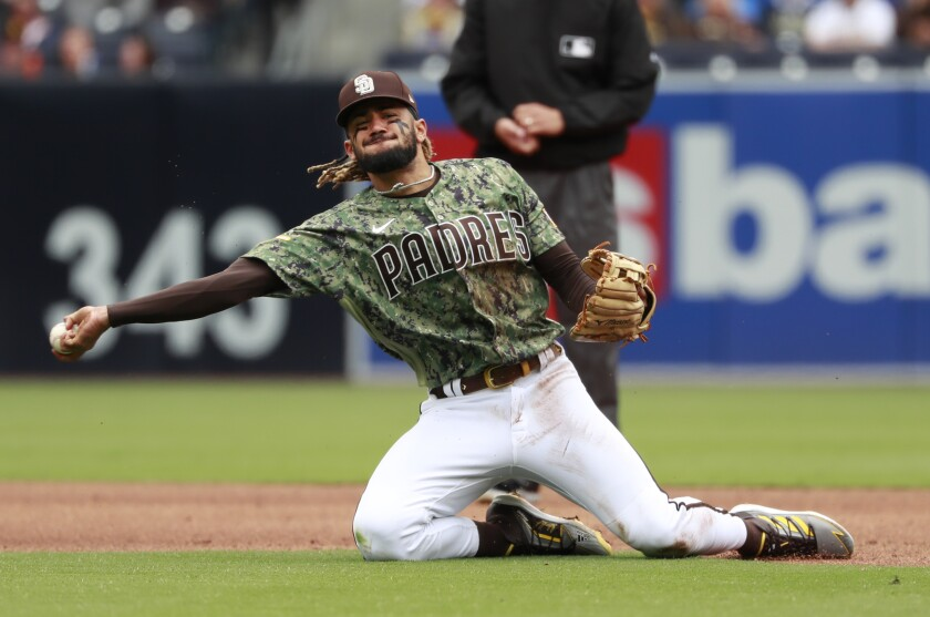 Padres shortstop Fernando Tatis Jr. throws out a Giants runner from his knees on May 2.
