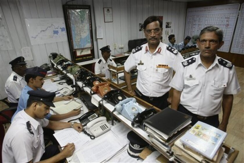 Mumbai Fire Brigade's Chief Fire Officer A.V. Sawant, standing second right, and Joint Chief Fire Officer P.D. Karguppikar, right, pose inside the control room of the Mumbai Fire Brigade in Mumbai, India, Sunday, Dec. 7, 2008. More than 20 people were honored Saturday by city officials for heroism during the Nov. 26 attacks on landmarks across Mumbai. (AP Photo/Gautam Singh)