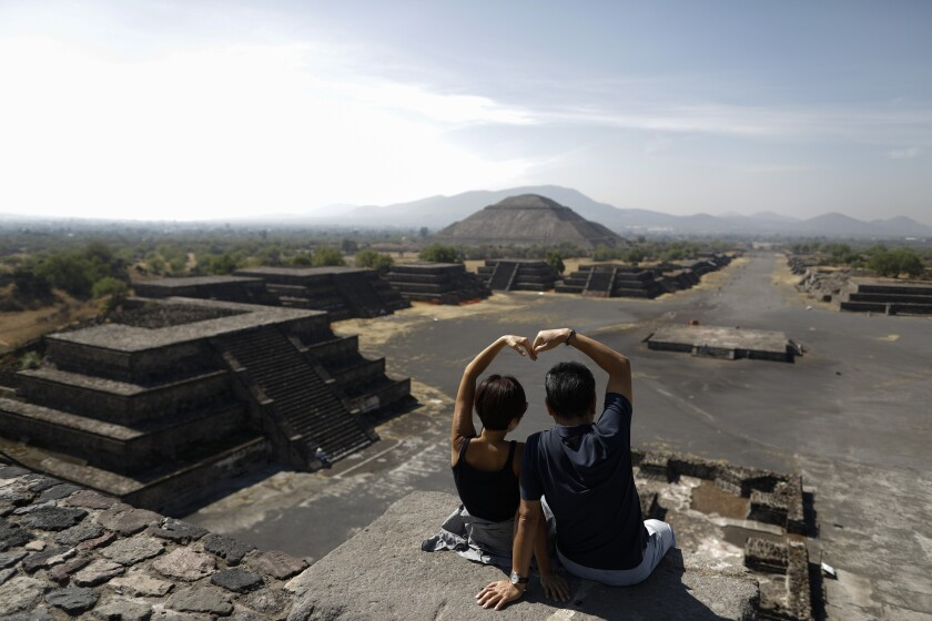 South Korean tourists Myung Hee Lee, left, and Byung Ho Im, form a heart with their hands as they pose for pictures atop the Pyramid of the Moon, in Teotihuacan, Mexico, Thursday, March 19, 2020. The pair took advantage of getting stuck in Mexico City for a day to visit the pyramids, after their flight home from a vacation in Cancun and Cuba was cancelled. To slow the spread of the new coronavirus, authorities announced Wednesday that they would close the pyramid complex on weekends, beginning Saturday, March 21, when thousands of visitors typically climb the Pyramid of the Sun to celebrate the Spring equinox.(AP Photo/Rebecca Blackwell)