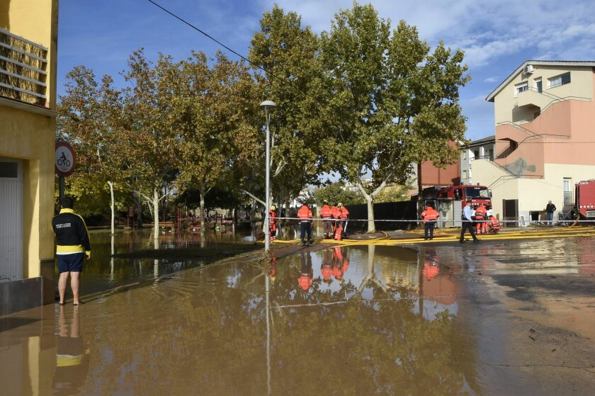 Emergency workers attended the scene where five residents were rescued and hospitalized after the rain engulfed a ground floor of the building next to the Sio River in the town of Agramunt, in Lerida province, Spain, Tuesday, Nov. 3, 2015. A river in northeastern Spain swelled by torrential downpou