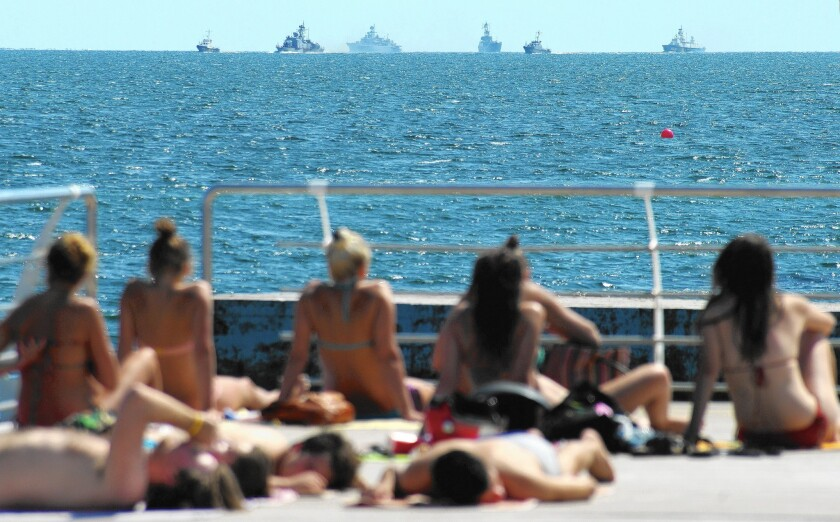 Sunbathers in the southern Ukrainian city of Odessa watch in August as Ukrainian navy ships take part in exercises.