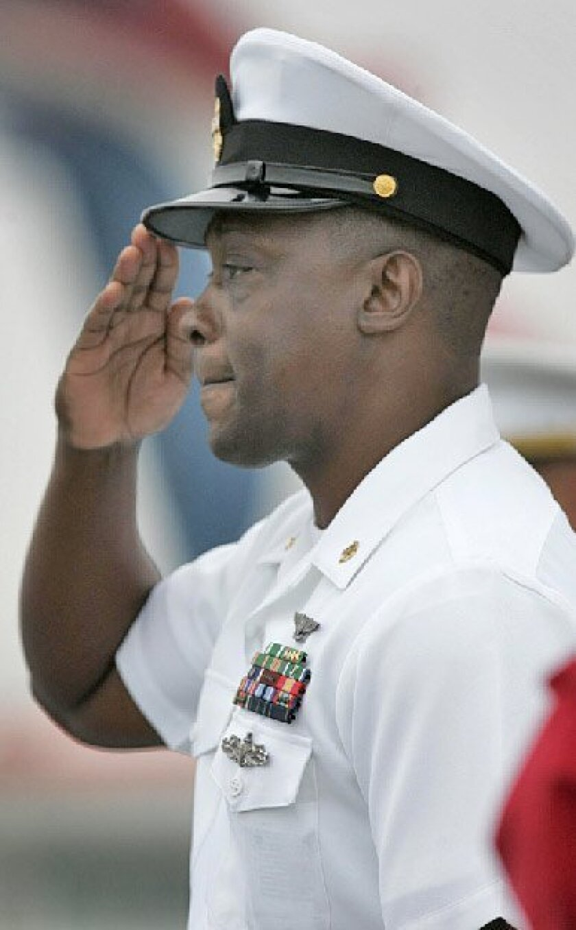 Master Chief Calvin Smith saluted his five fallen comrades at a memorial service yesterday honoring the victims of a May 19 helicopter crash. (John Gibbins / Union-Tribune)