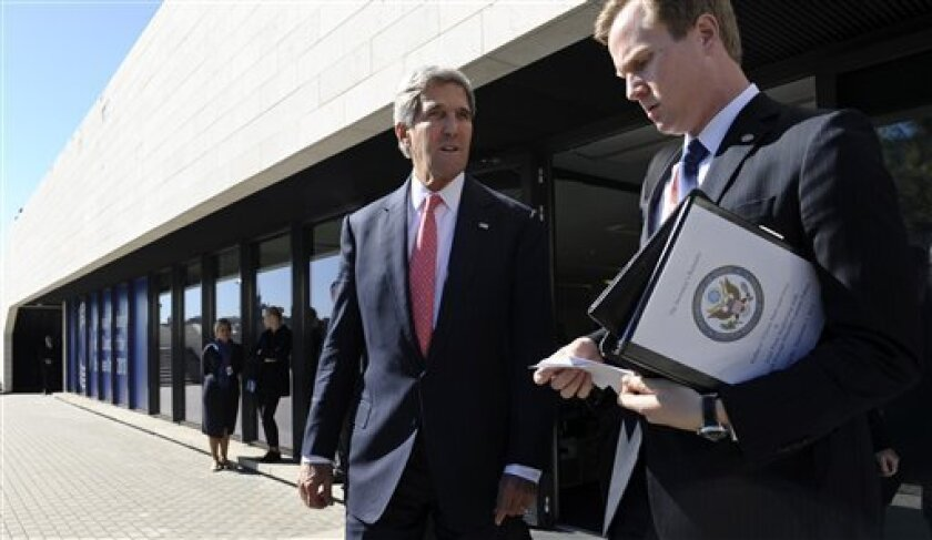 US Secretary of State John Kerry, centre, with aide Jason Meininger as he leaves a meeting with European Union Ministers of Foreign Affairs at the National Gallery of Art in Vilnius, Lithuania, Saturday, Sept. 7, 2013. Kerry traveled to Europe to court international support for a possible strike on the Syrian regime for its alleged use of chemical weapons while making calls back home to lobby Congress where the action faces an uphill battle. (AP Photo/Susan Walsh, Pool)