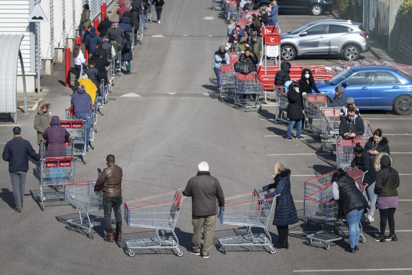 Shoppers line up outside a Costco in London in March, as people continue to stock up on food amid the coronavirus pandemic.