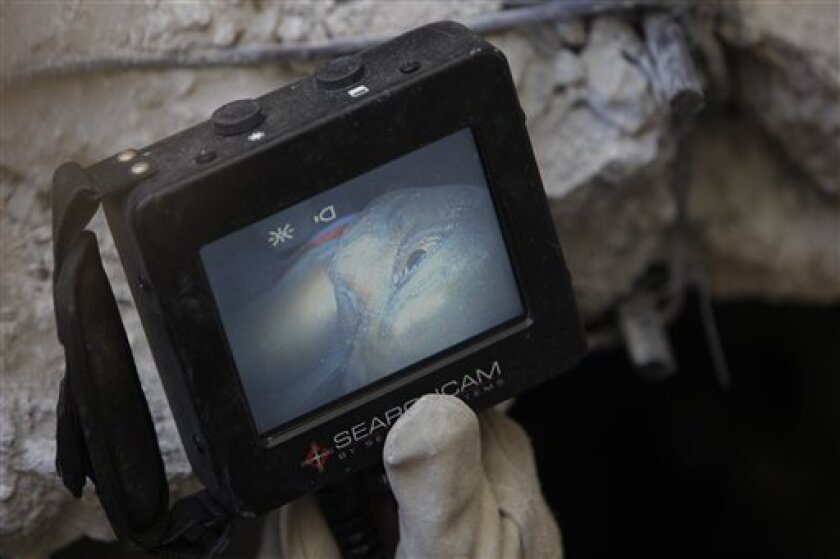 U.S. rescue worker Sam Grey, of the Fairfax County Urban Search and Rescue, holds a monitor showing a woman, Jean Luis Sainte Heleine, 28, alive and conscious, buried under the collapsed University of Port-au-Prince, Saturday, Jan. 16, 2010. (AP Photo/Gregory Bull)