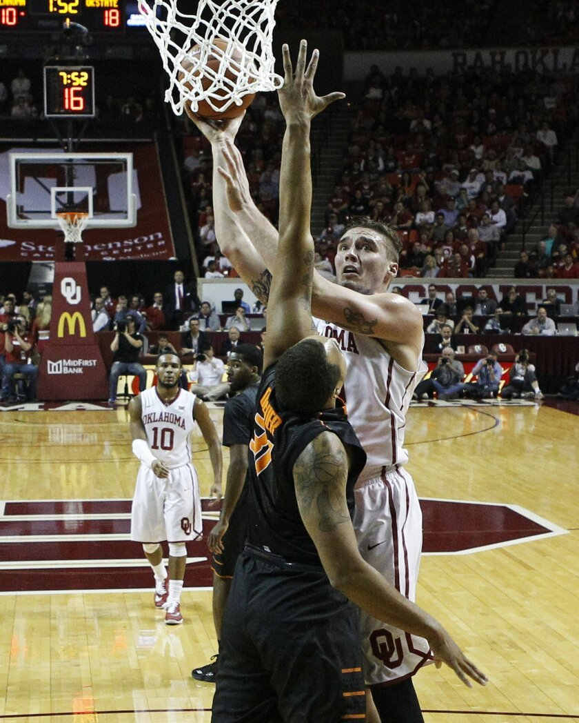 Oklahoma forward Ryan Spangler, right, shoots over Oklahoma State forward Chris Olivier during the first half of an NCAA college basketball game in Norman, Okla., Wednesday, Feb. 24, 2016. (AP Photo/Sue Ogrocki)