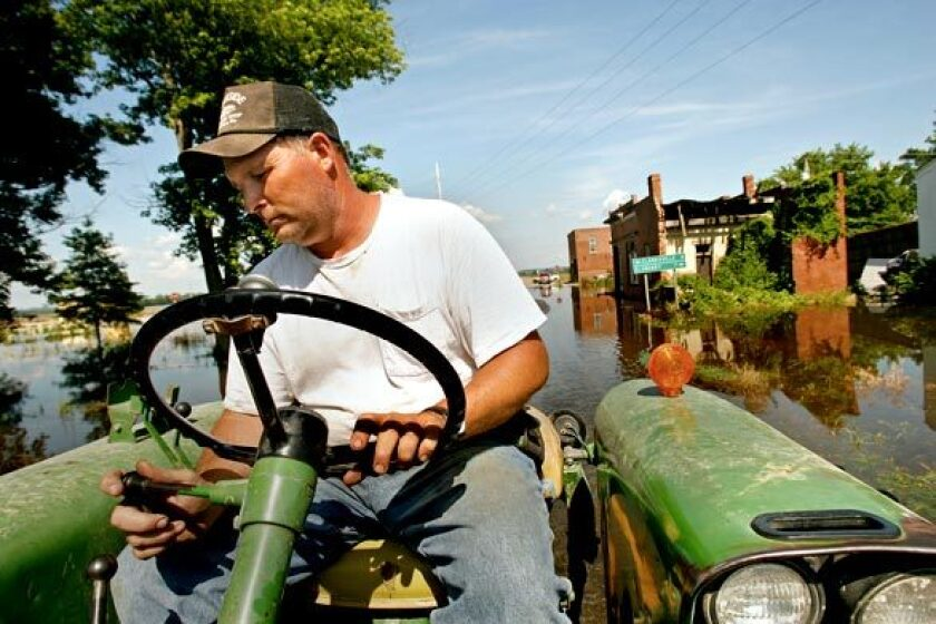 """Bill Hunter drives his tractor through the floodwaters in Annada, Mo. His family owns 1,000 acres that are now under water. """"We went from drought to this,"""" Hunter said. """"it's a mess."""""""