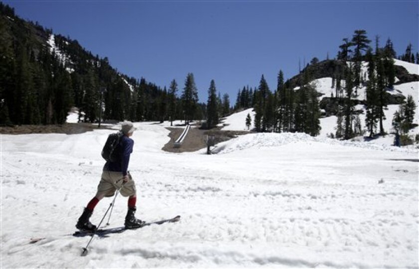 Local resident Jeff Cole, makes his way across a snow covered field as he goes for a ski run at Alpine Meadows Ski Resort near Tahoe City, Calif., Thursday, June 30, 2011. An unusually cold and wet year, which continues to bring snow to California's mountains, is enabling Alpine Meadows to be open