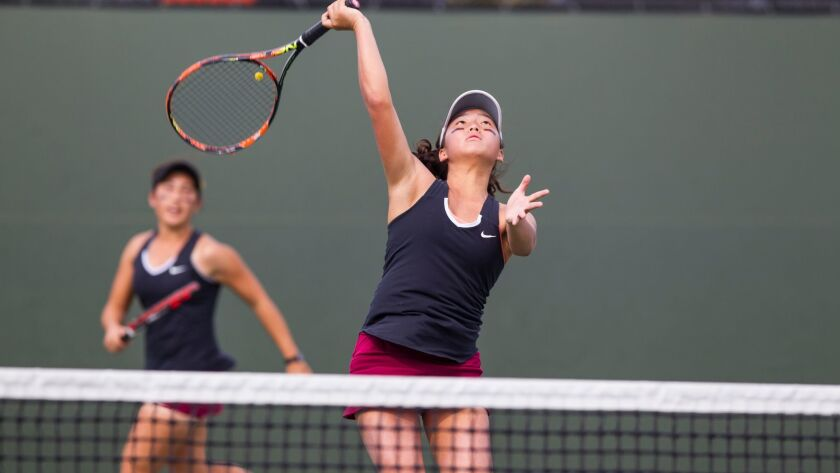Torrey Pines' YJ Lee hits an overhead in front of partner Lily Nilipour. The two combined for a marathon win in doubles.