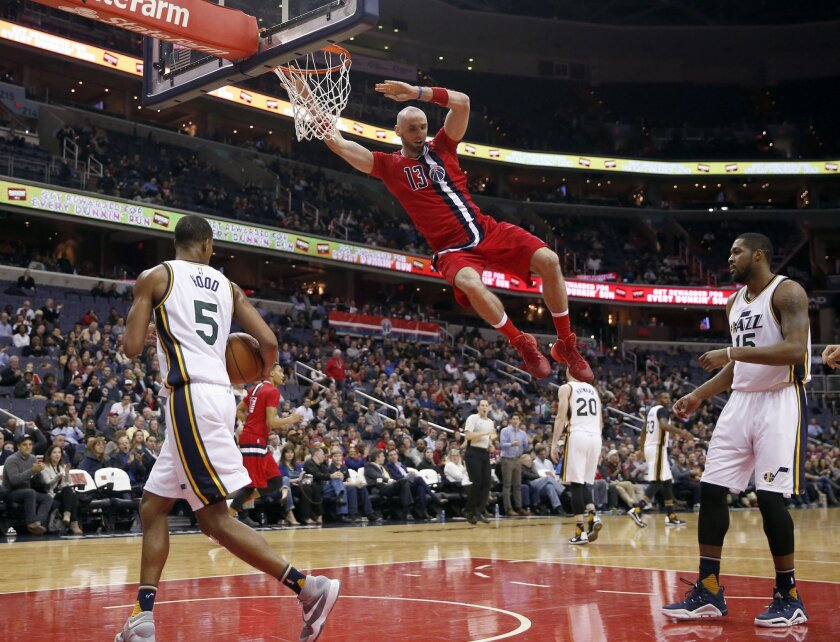 Washington Wizards center Marcin Gortat (13), from Poland, hangs from the rim after his dunk in front of Utah Jazz guard Rodney Hood (5) and forward Derrick Favors during the first half of an NBA basketball game Thursday, Feb. 18, 2016, in Washington. (AP Photo/Alex Brandon)