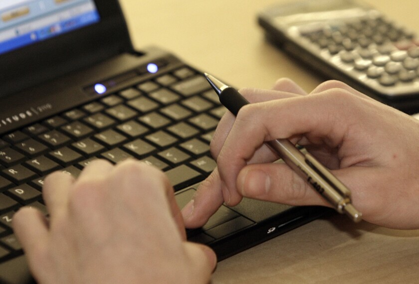 A person types on a laptop. Legislation could end Bureau of Prisons' unjust monitoring of inmate-attorney emails.