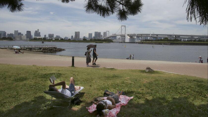 A man reads at a park in Tokyo's Daiba bay area, Tuesday, July 3, 2018. (AP Photo/Koji Sasahara)