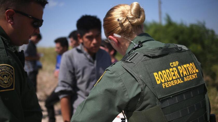 Foto de archivo de un oficial de la Patrulla Fronteriza deteniendo a un inmigrante.