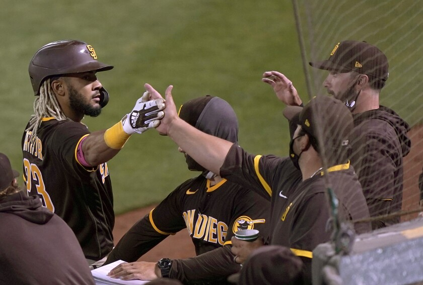 Fernando Tatis Jr. is congratulated by teammates after scoring against the A's last night.