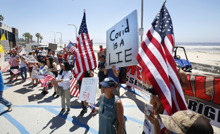 Protesters gather near the boardwalk in Pacific Beach during A Day of Liberty rally on Sunday, April 26, 2020. The protesters were against the government shutdown due to the coronavirus.